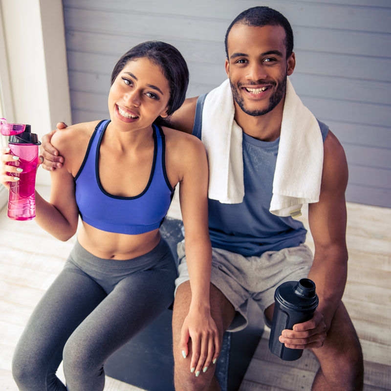 couple holding their drinks after a workout