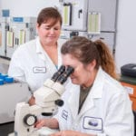 woman checking a product through a microscope